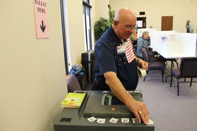 """Poll worker Gary Kaltenbach leaves """"I Love Voting"""" stickers for voters returning ballots at Grace Community Church."""