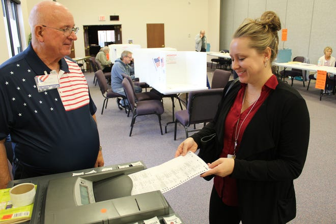 Poll worker Gary Kaltenbach watches as Allison Eaglen, of Ballville Township, submits her ballot Tuesday at Grace Community Church.