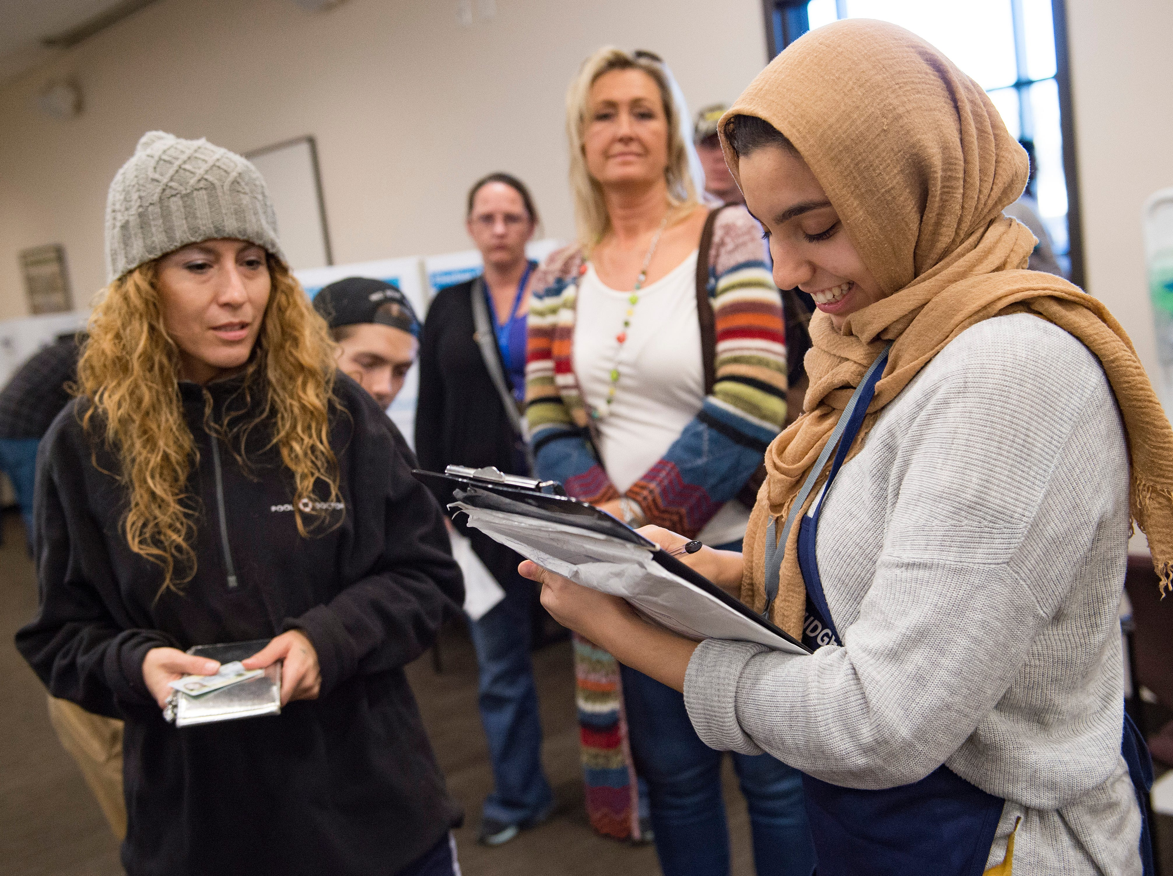 Volunteer Malak Shawesh records voter wait times as people line up to cast their ballot at the Larimer County Courthouse on Election Day, Monday, November 6, 2018. Wait times hovered around 15 minutes by 3 p.m. on Election Day.