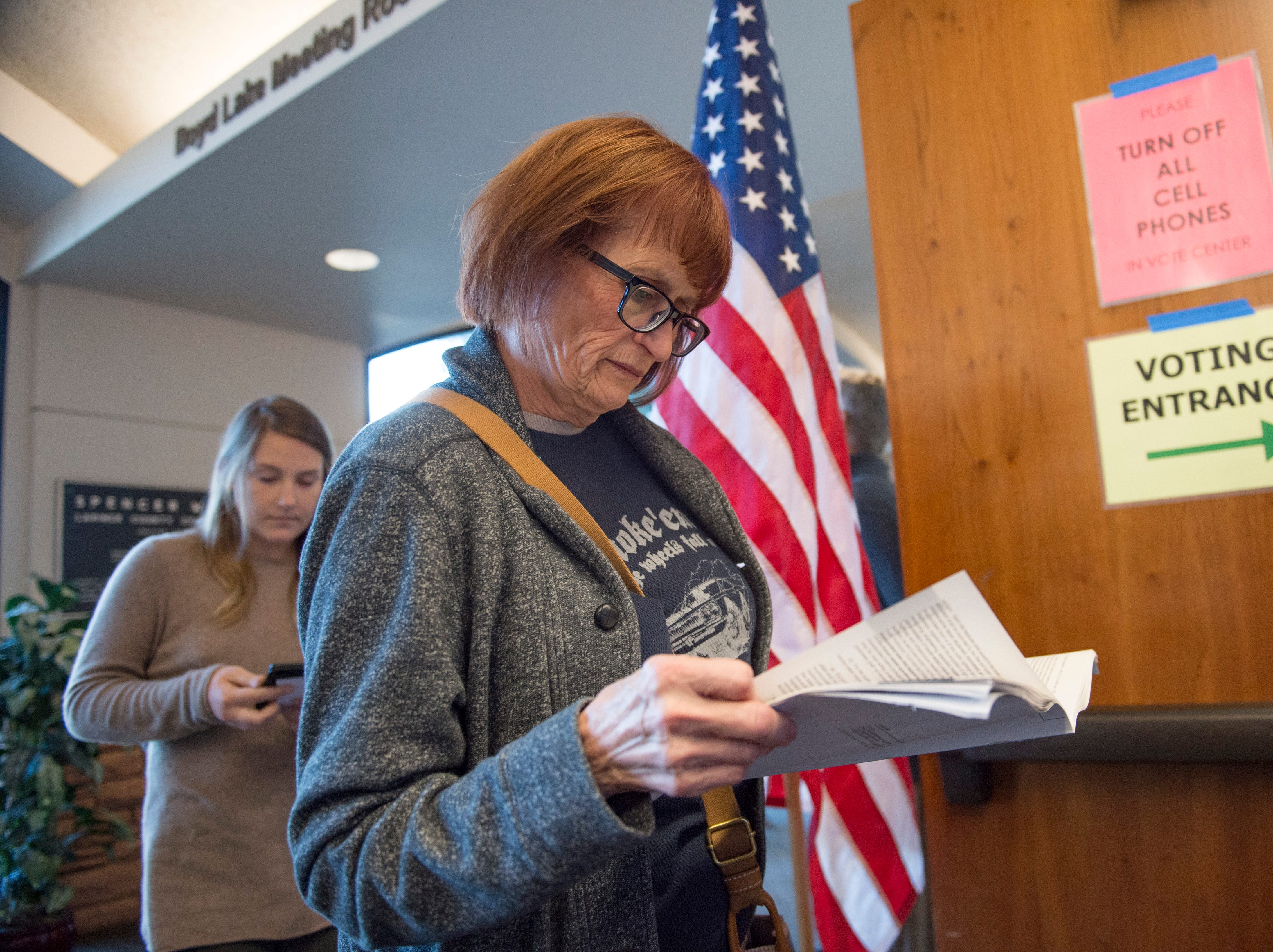 Christine Feldbush reviews a voter's guide as she waits in line to cast her ballot at the Larimer County Courthouse on Election Day, Monday, November 6, 2018.
