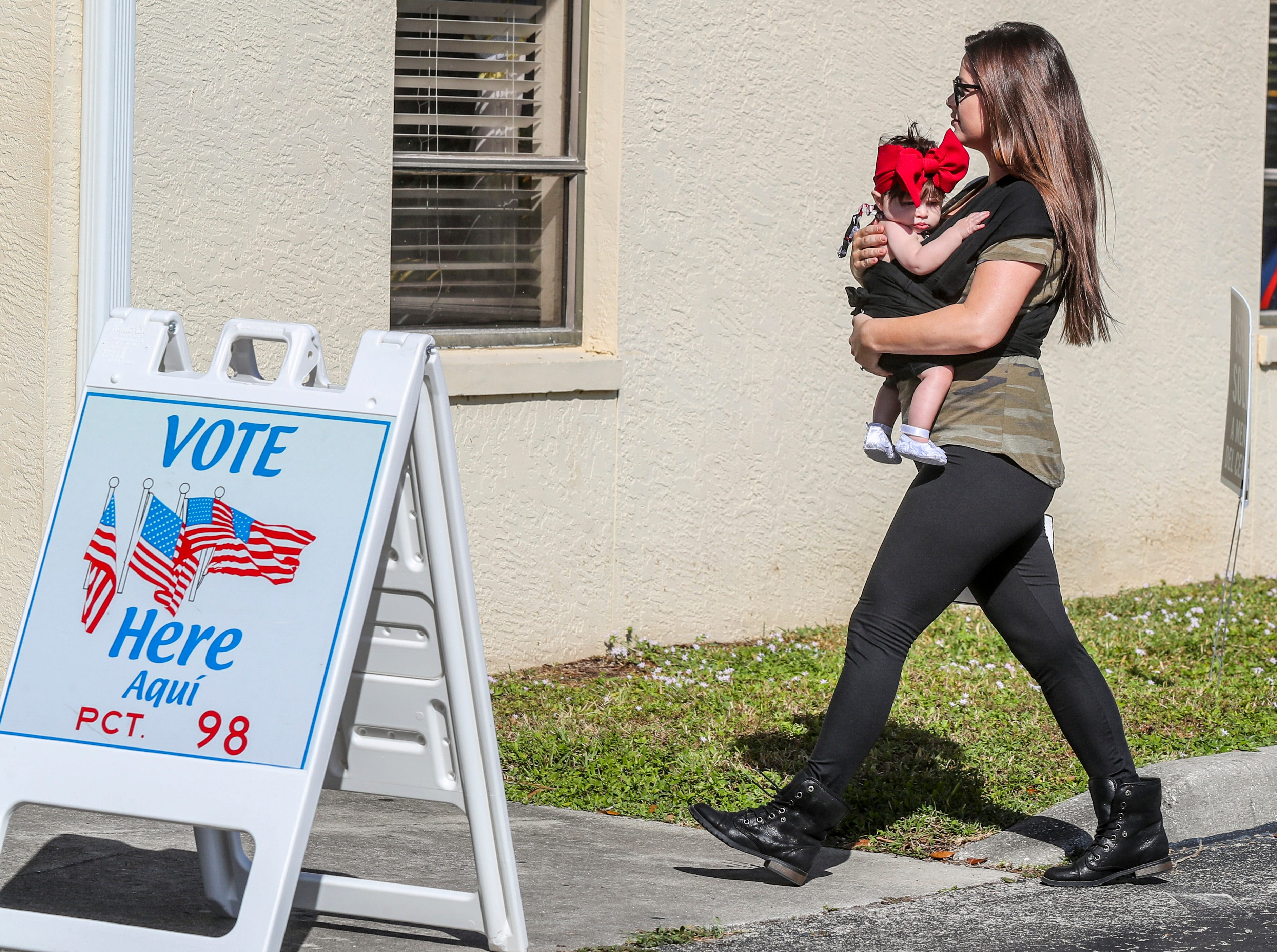 A voter walk into Precinct 98 in Cape Coral to vote with her young daughter in tow.