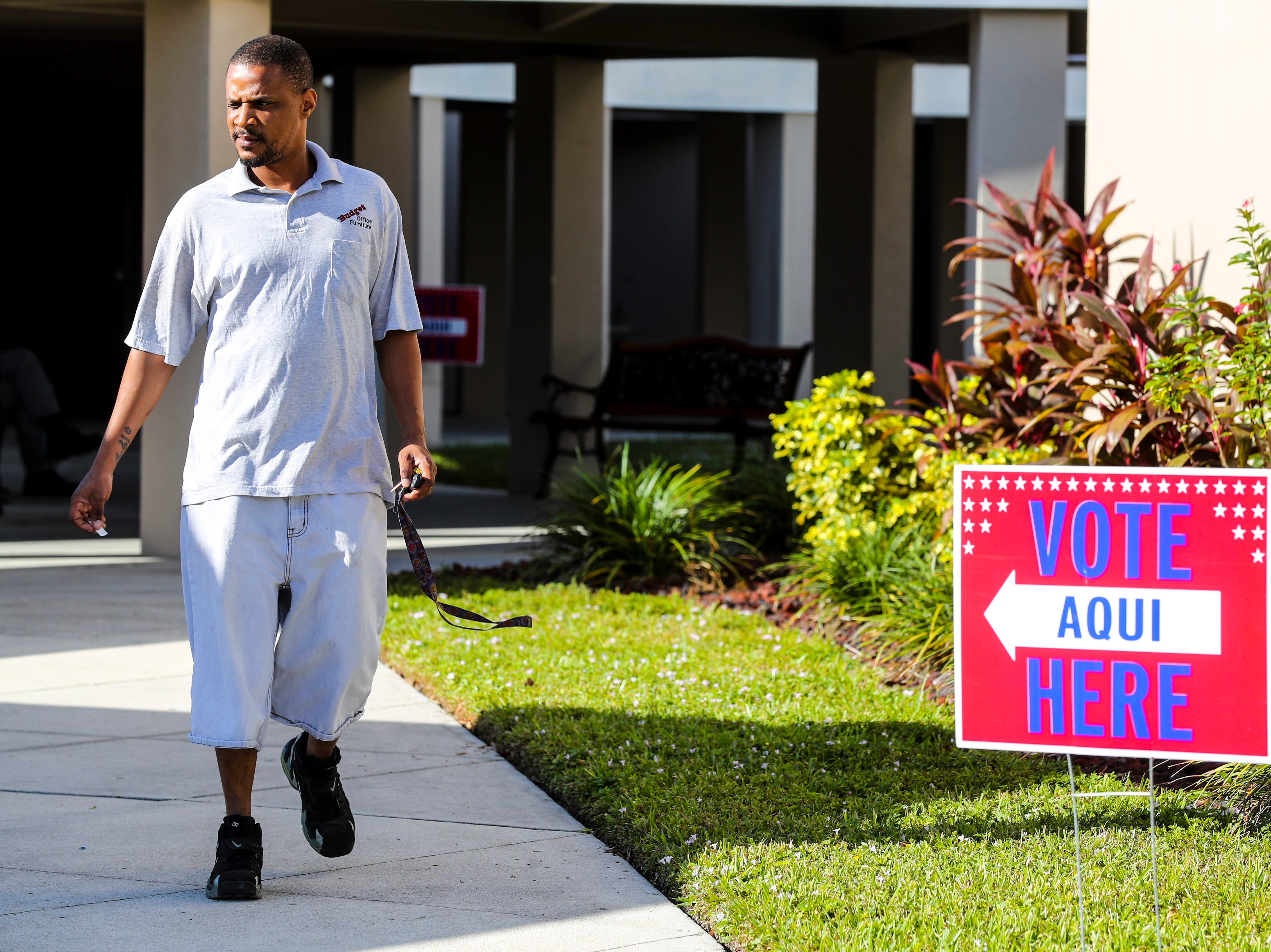 Voters head in and out of Precinct 9 sign in Fort Myers as they exercise their right to vote.