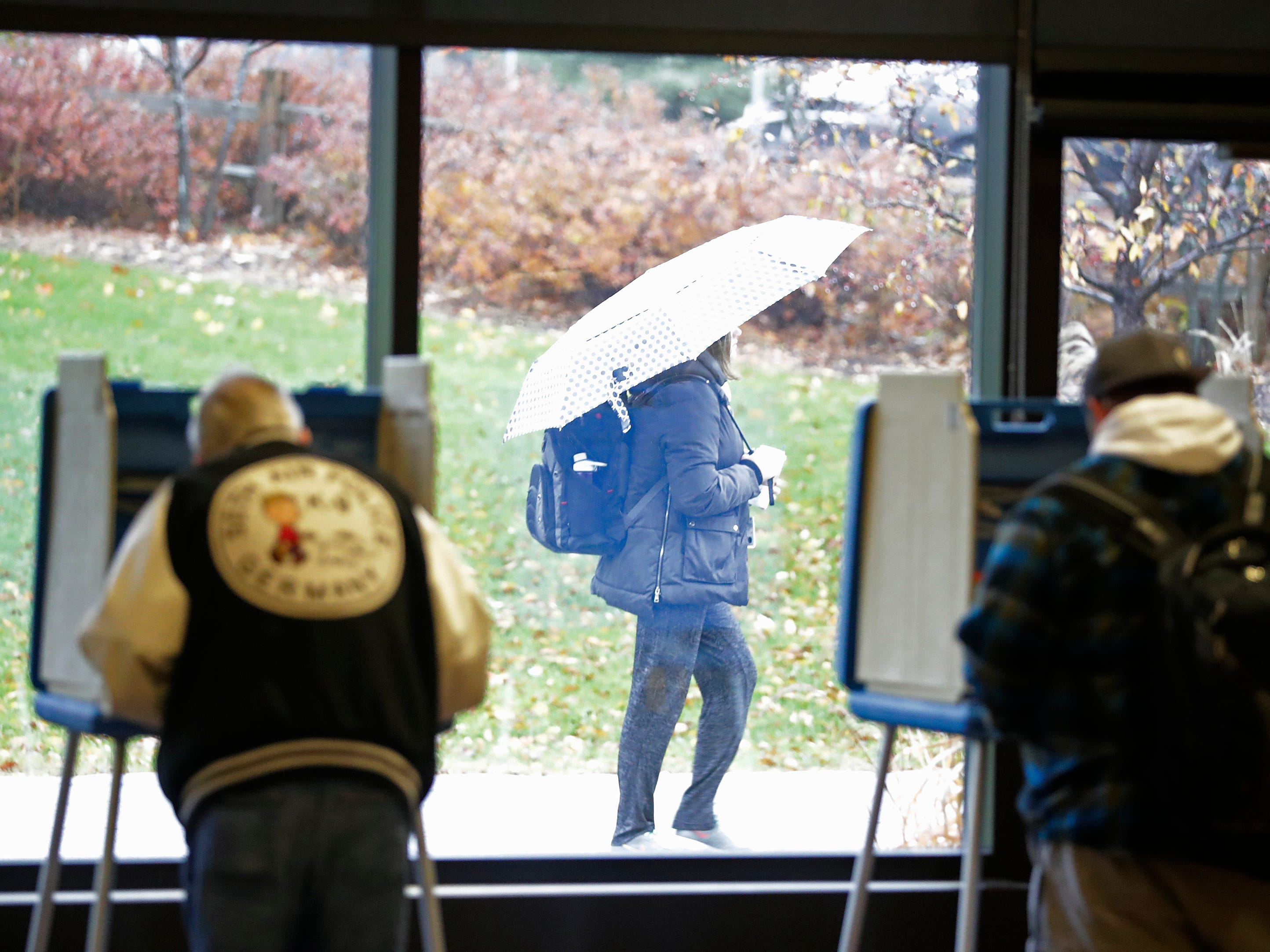 A student walks past as voters cast their ballots at the UW-Green Bay campus on Tuesday, November 6, 2018, in Green Bay, Wis.