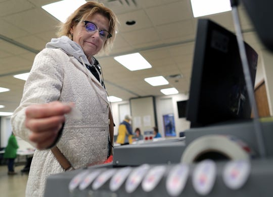Patti Roovers takes an I Voted sticker after casting her ballot in the midterm elections at Prince of Peace Lutheran Church on Tuesday, November 6, 2018, in Appleton, Wis.