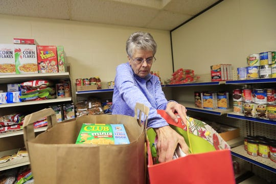 Volunteer Judy Lom fills bags full of food during distribution from the food pantry at Trinity Lutheran Church in Green Bay.