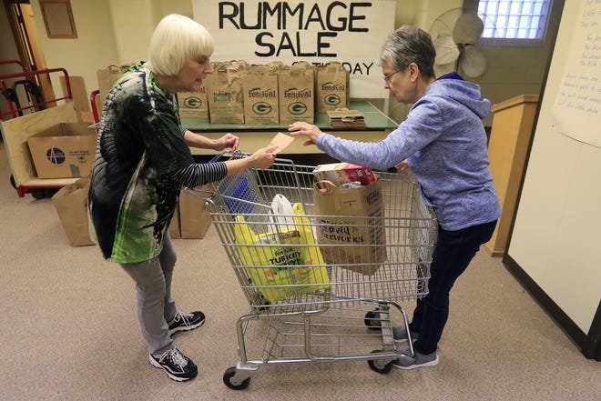 Volunteers Sharon Millar (left) and Judy Lom prepare a cart of food full of food during distribution from the food pantry at Trinity Lutheran Church in Green Bay.