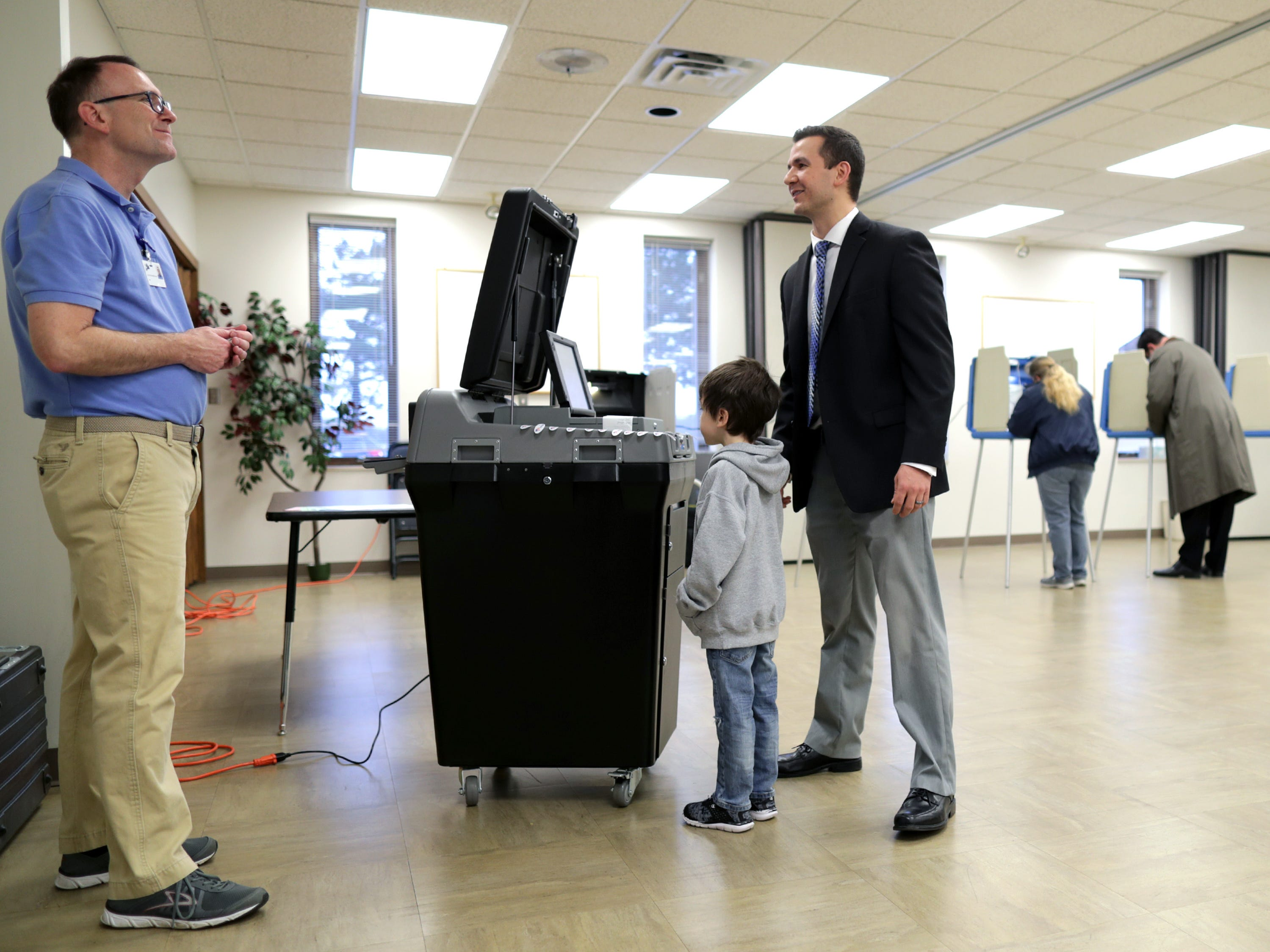 Chief Elections Inspector Alan Stewart, left, talks with Mike Slowinski and his son Abraham as voters cast their ballots in the midterm elections at Prince of Peace Lutheran Church on Tuesday, November 6, 2018, in Appleton, Wis.