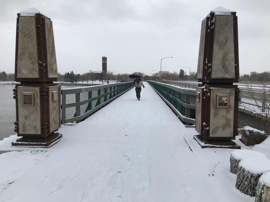 Albert Remington walks crosses the Missouri River Tuesday morning in Great Falls as the snow flies.