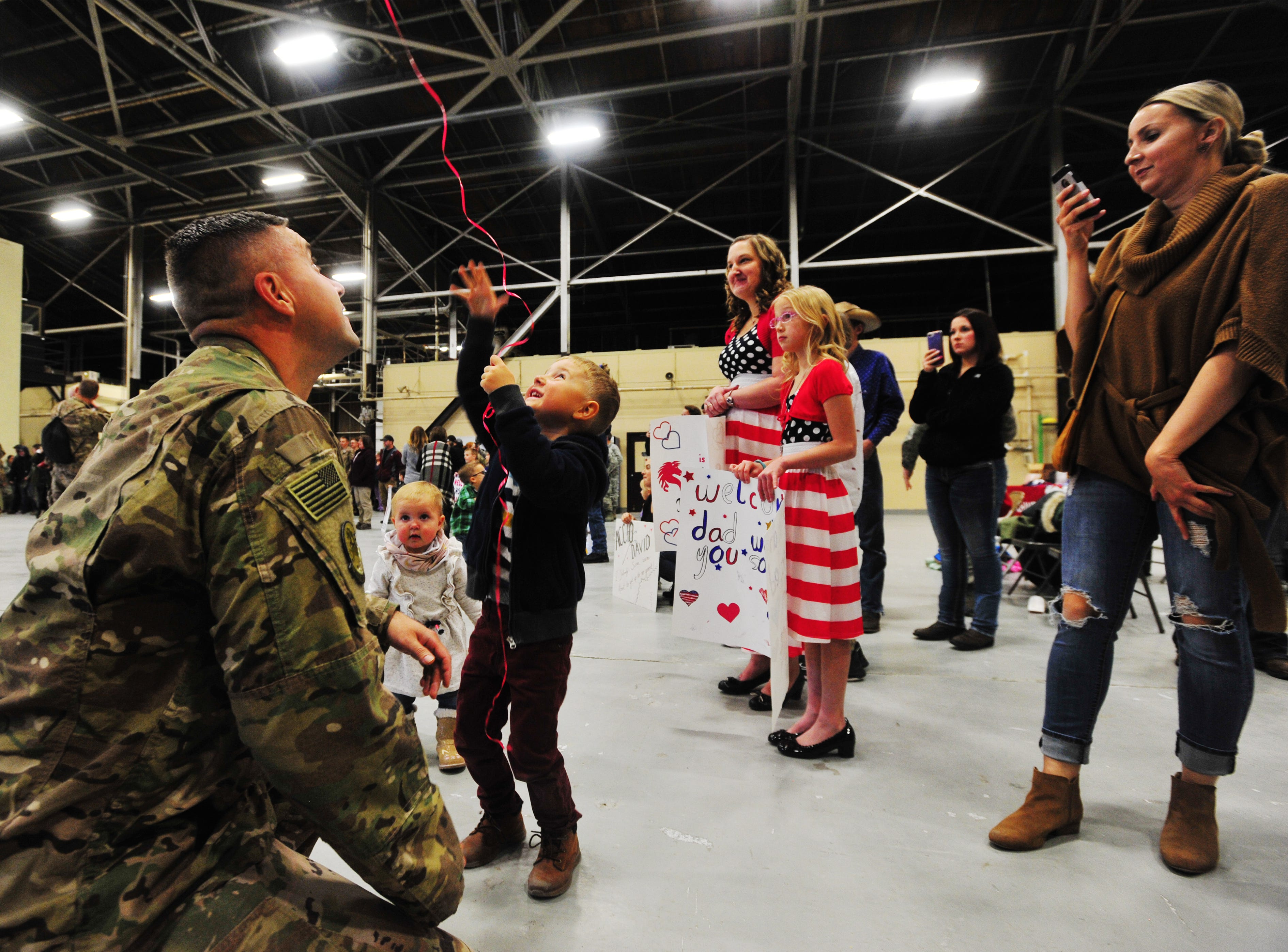 Tech Sergeant Tomasz Idzi plays with his son Victor, age 4, in a hanger at Malmstrom Air Force Base on Monday.  Idzi was one of 100 members of the 819th Red Horse Squadron who returned to Malmstrom Air Force Base after a seven month deployment to the African country of Niger.