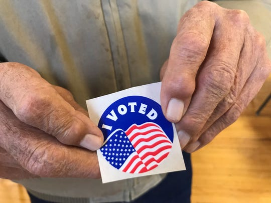 "Vern Kuka holds his ""I Voted"" sticker in Valier after voting with his wife Marie."