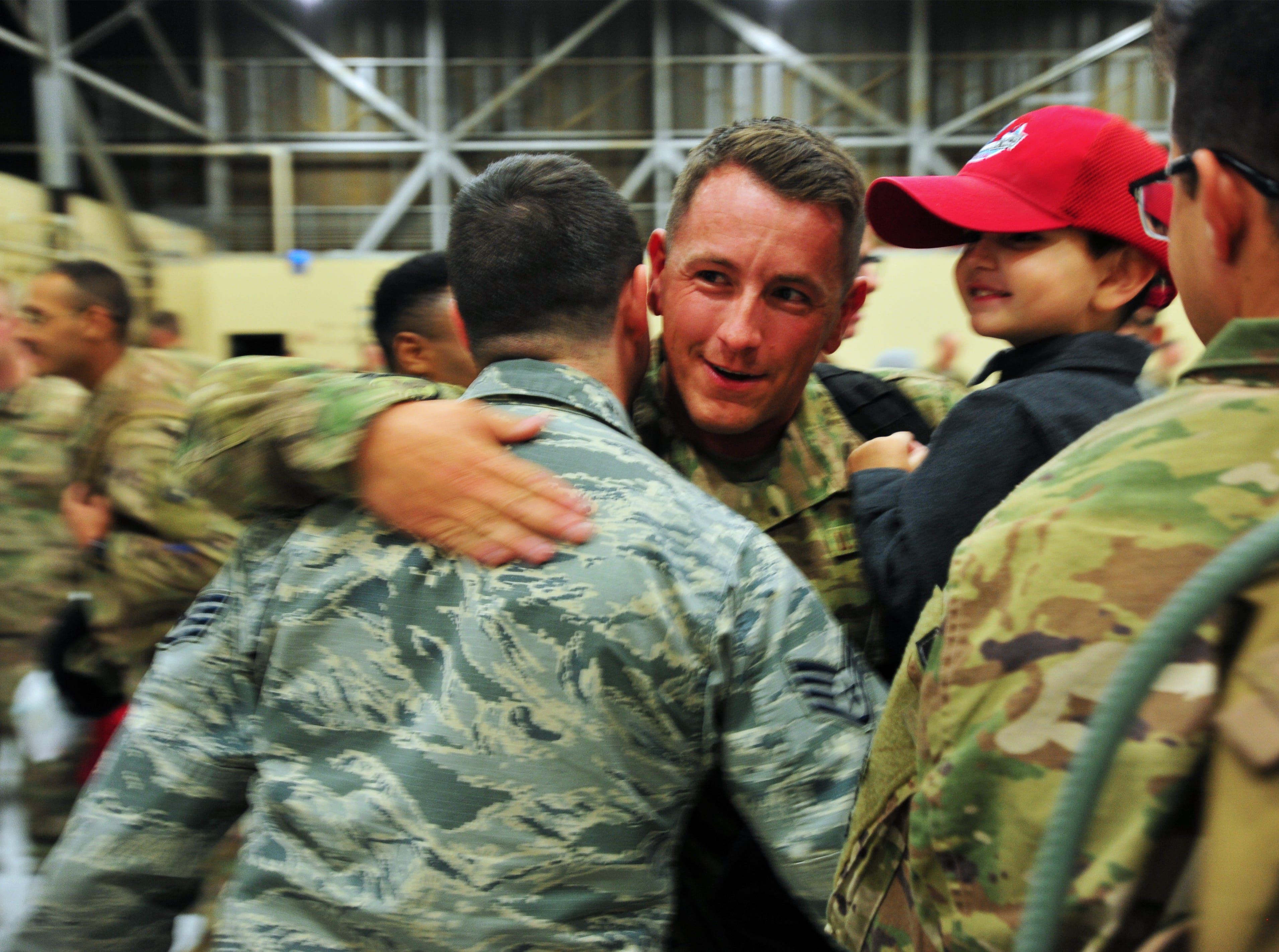 Staff Sergeant Verick McCorkell is welcomed home by his son Vaughn, age 4, and colleagues on Monday afternoon at Malmstrom Air Force Base.  McCorkell was one of 100 members of the 819th Red Horse Squadron who returned home, Monday, after a seven month deployment to the African country of Niger.