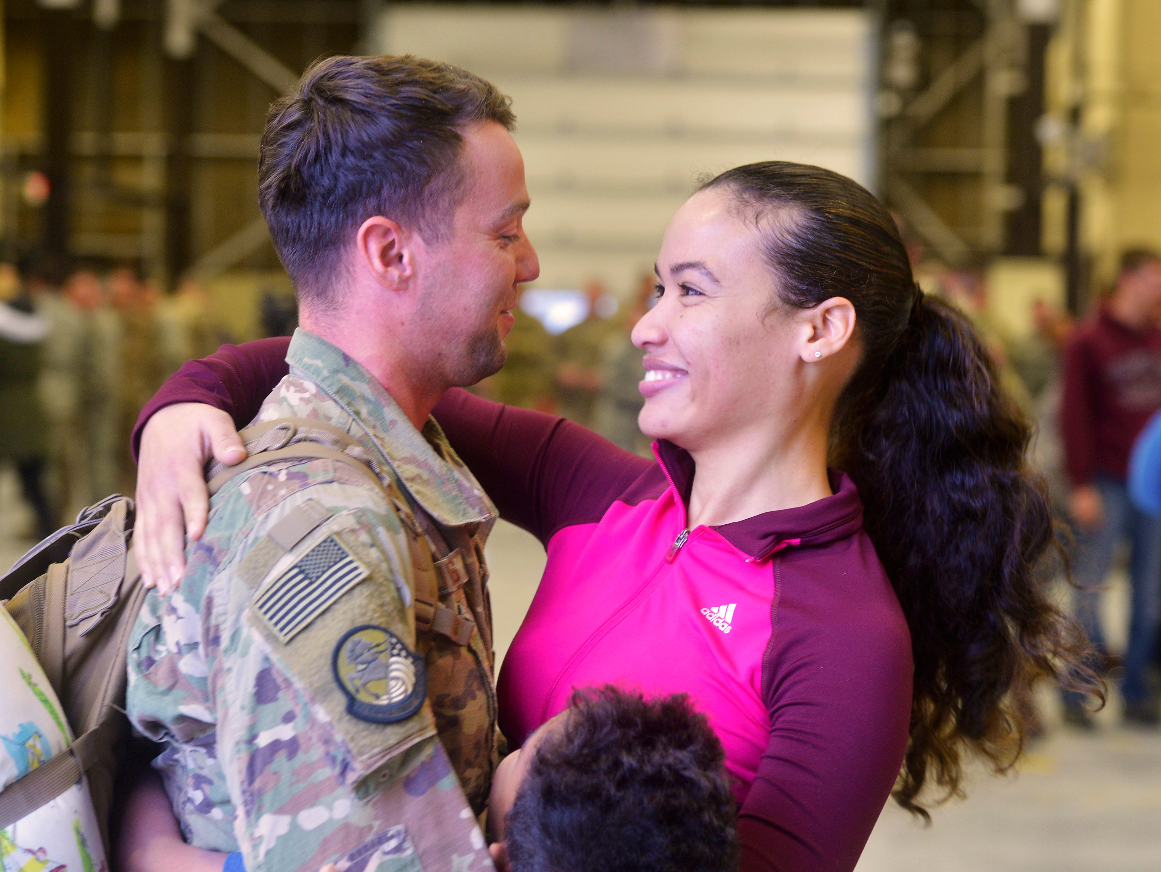Staff Sergeant Dylan Kalivas is greeted by his wife Any Cuello-Kalivas and step-son David on Monday afternoon at Malmstrom Air Force Base.  Kalivas was one of 100 members of the 819th Red Horse Squadron who returned home, Monday, after a seven month deployment to the African country of Niger.