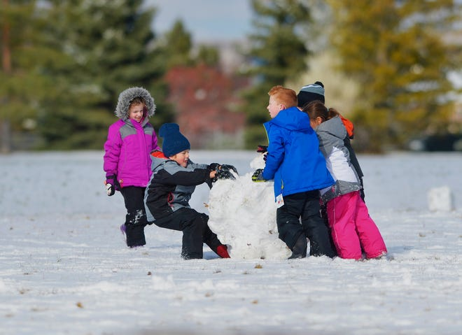 Meadow Lark Elementary School first-graders build a snowball during recess Tuesday after 1.2 inches of snow fell in Great Falls.