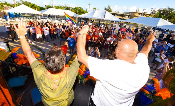 Democratic gubernatorial candidate, Lou Leon Guerrero, left, and her running mate, Joshua Tenorio, celebrate to the cheers of supporters and others at their campaign headquarters in Hagåtña during the early morning hours of Wednesday, Nov. 7, 2018.