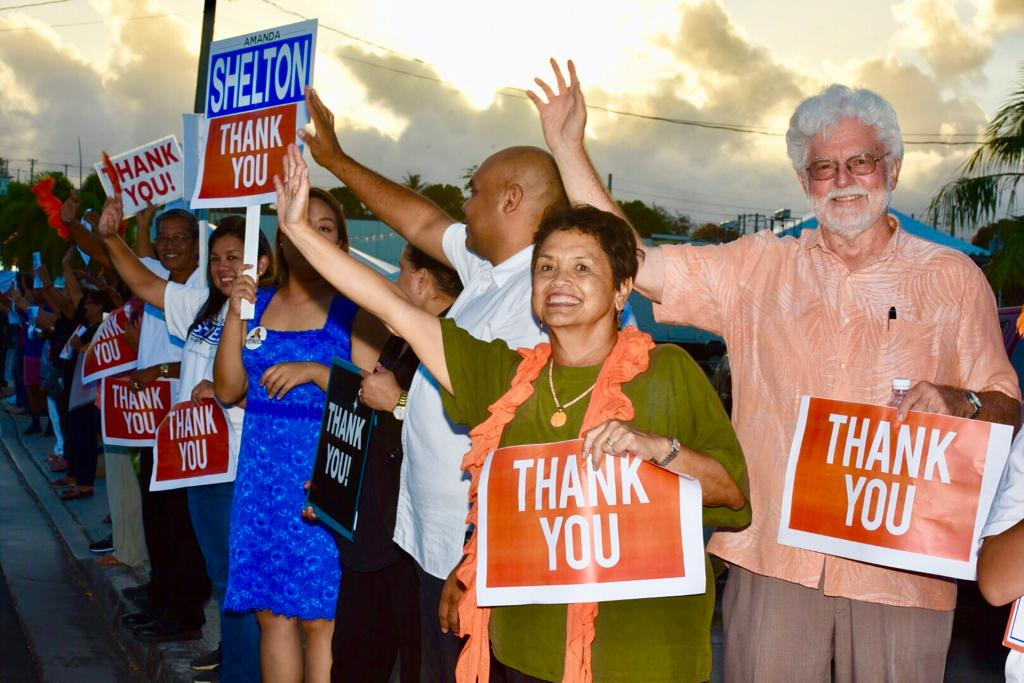 Gubernatorial front-runner Lou Leon Guerrero, center, her running mate Josh Tenorio, behind her, her husband Jeff Cook and others wave at motorists in Hagåtña as they await the final vote tally early Wednesday, Nov. 7, 2018.