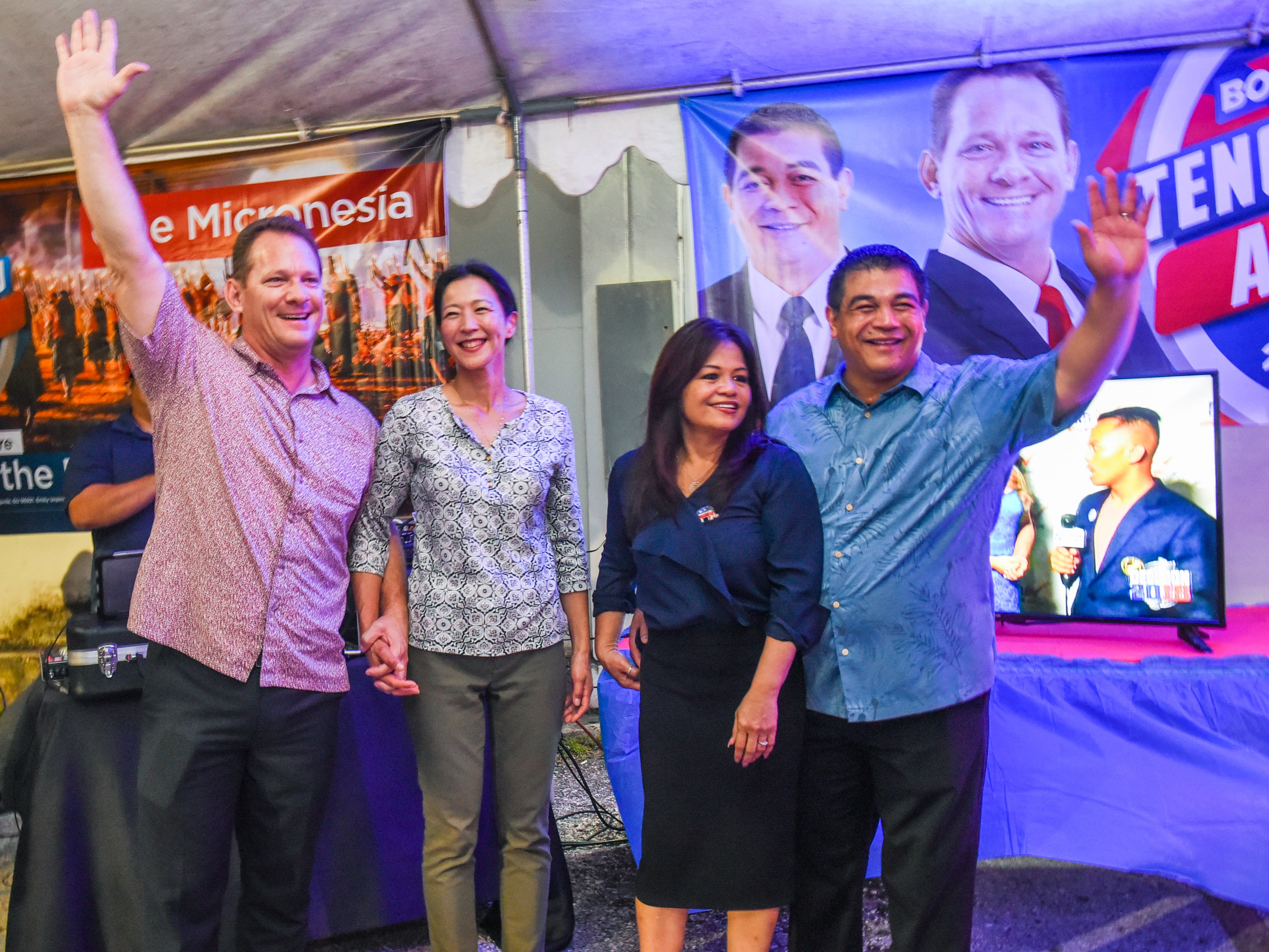 Republican gubernatorial candidate, Lt. Gov. Ray Tenorio, left, and his running mate Sen. Tony Ada, are joined by their wives, Madoka Tenorio and Annette Ada, as they wave to cheering supporters at the team's Tamuning campaign headquarters during the early morning hours of Wednesday, Nov. 7, 2018.