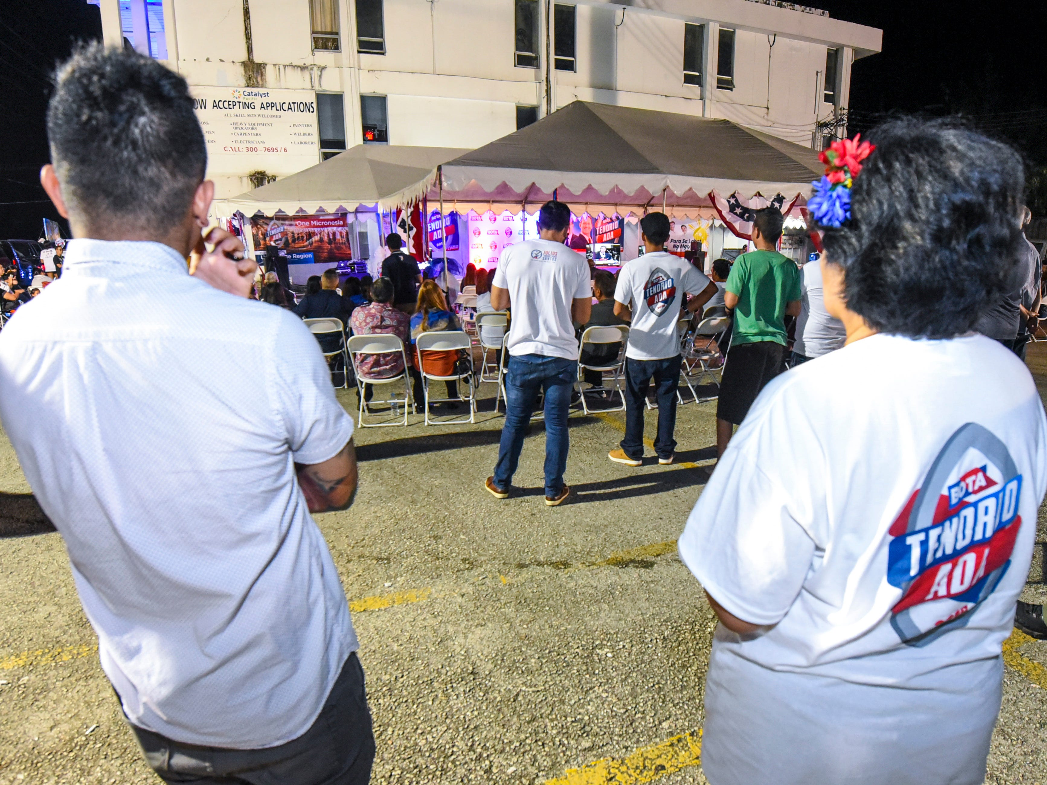 Supporters of the Republican gubernatorial team of Lt. Gov. Ray Tenorio and Sen. Tony Ada listen to the results of the latest election returns outside the team's campaign headquarters in Tamuning during the early morning hours of Wednesday, Nov. 7, 2018.