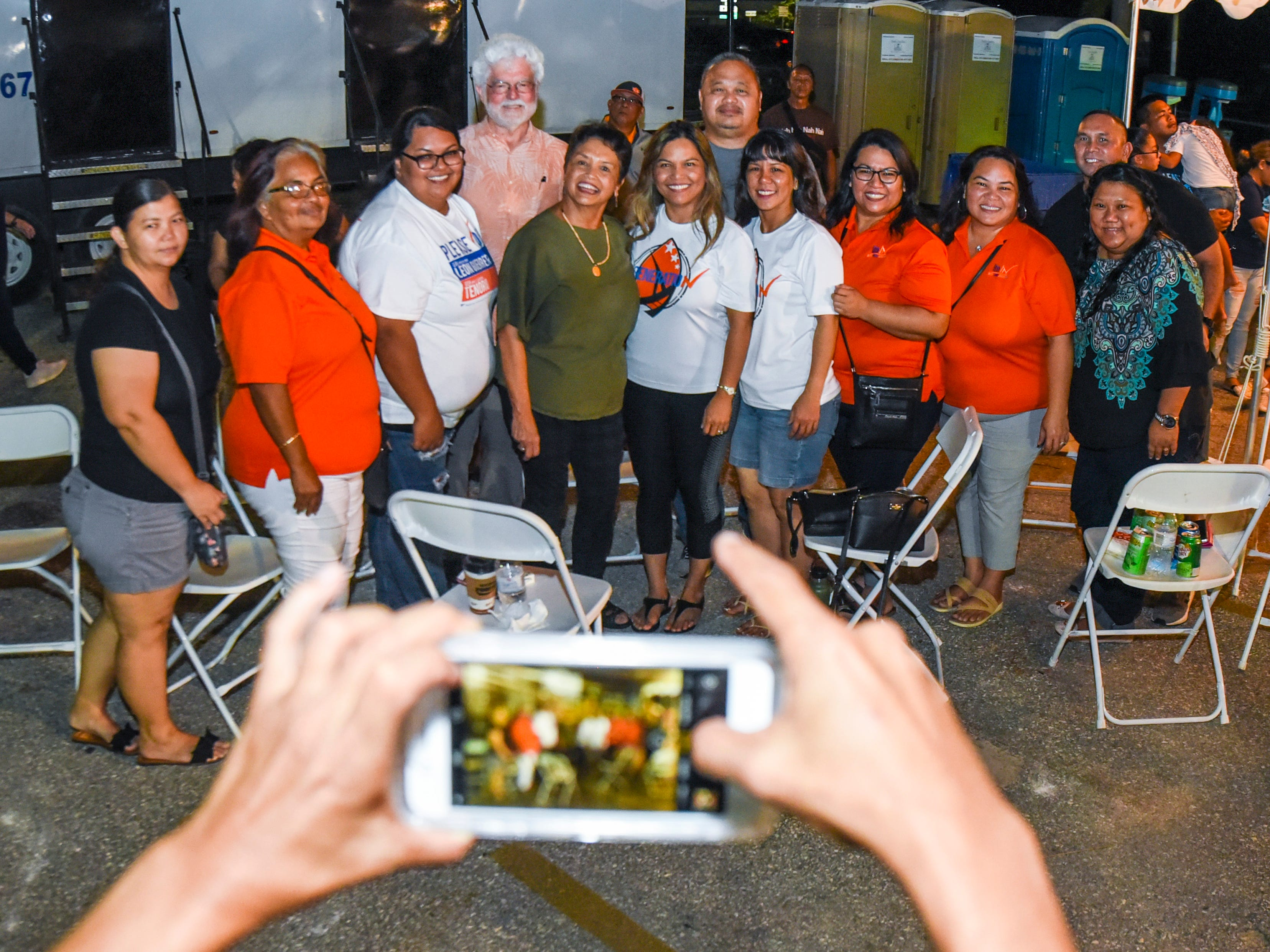 Democratic gubernatorial candidate, Lou Leon Guerrero, wearing green, celebrates supporters after favorable early returns at the team's campaign headquarters in Hagåtña during the late evening hours of Tuesday, Nov. 6, 2018.