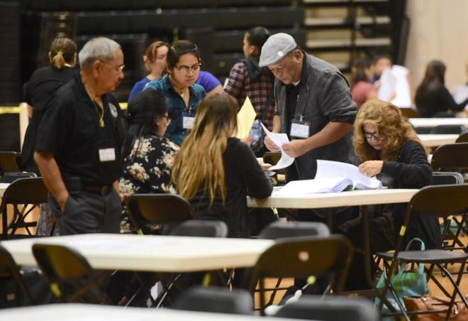 Precinct officials Tuesday evening reconcile general election ballots at the University of Guam Calvo field house.
