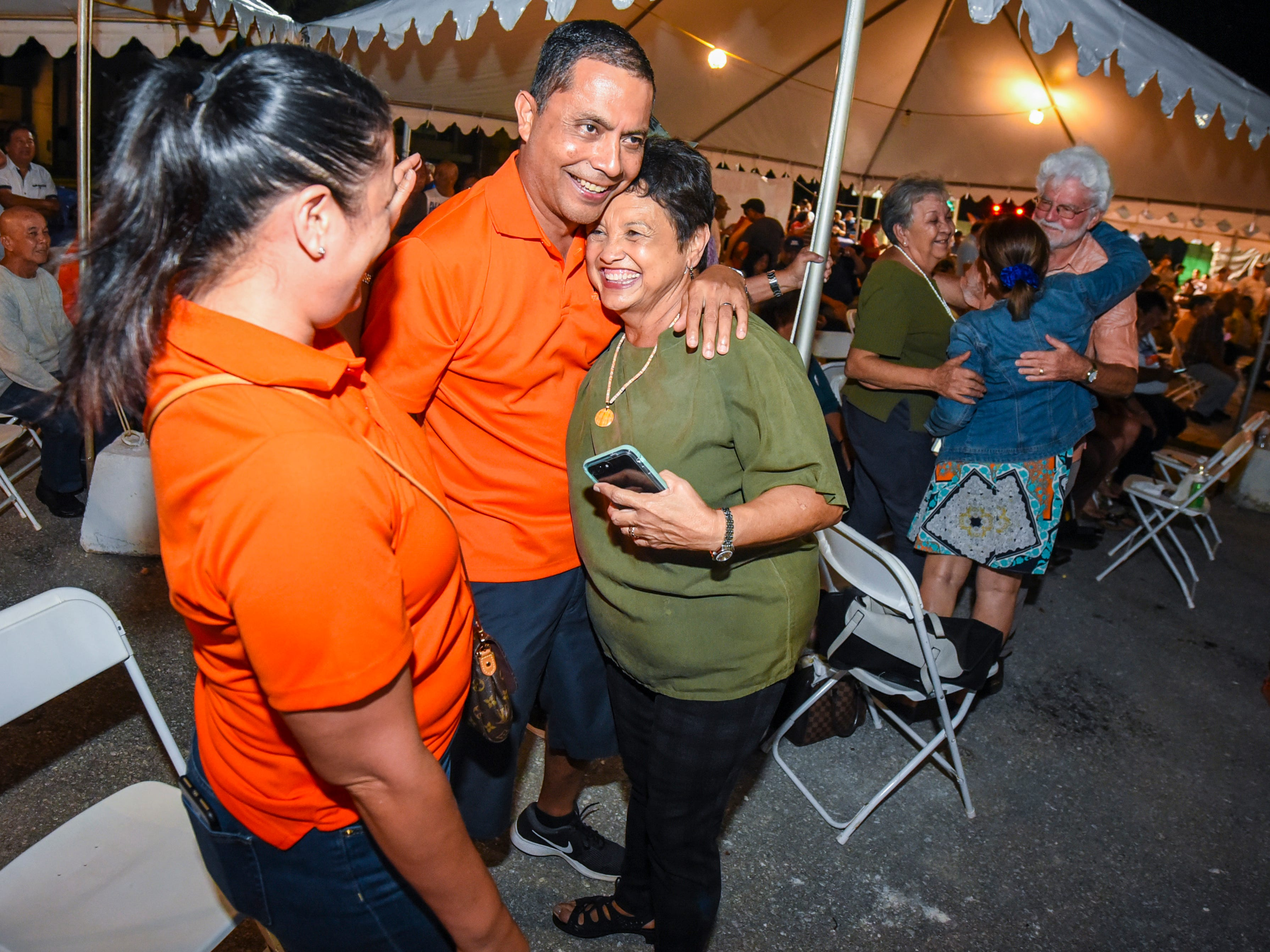 Democratic gubernatorial candidate, Lou Leon Guerrero, wearing green, celebrates with supporters after favorable early returns at the team's campaign headquarters in Hagåtña during the late evening hours of Tuesday, Nov. 6, 2018.