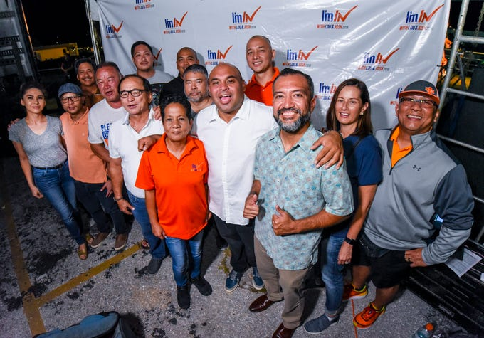 Democratic candidate for lieutenant governor, Joshua Tenorio, center, gathers with leading supporters and others at the team's campaign headquarters in Hagåtña during the early morning hours of Wednesday, Nov. 7, 2018.