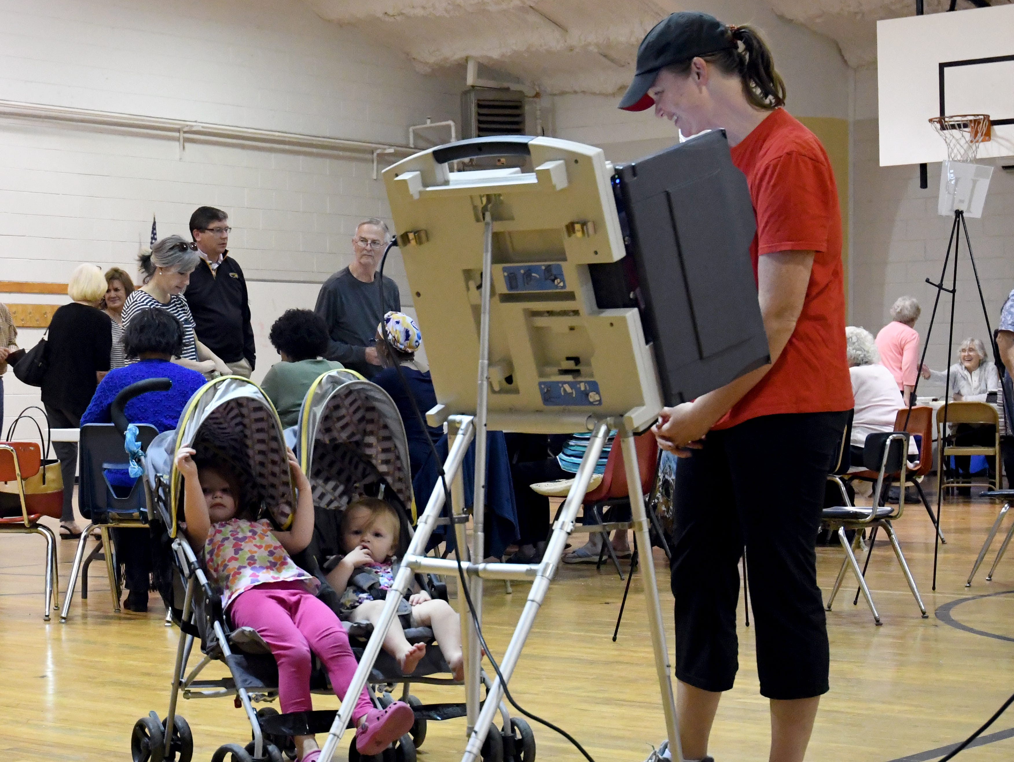 Hattiesburg resident resident Allison Smith looks at her children Kimberly, 3, and Catherine 1, as she votes during the midterm elections at the Thames Elementary precinct on Tuesday, November 6, 2018.