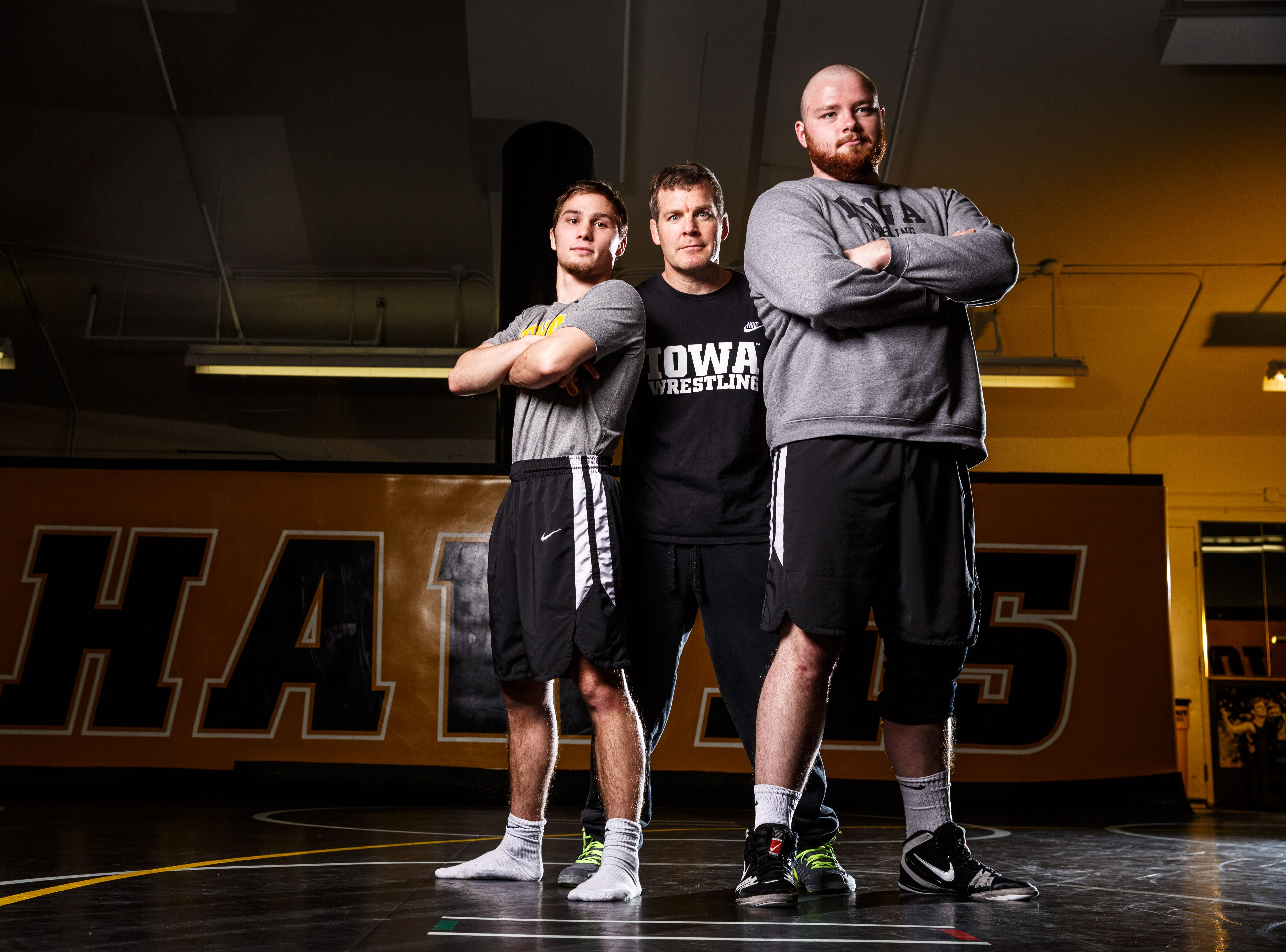 Head coach Tom Brands steps into a photo with Iowa wrestlers Spencer Lee and Sam Stoll during Iowa wrestling media dayMonday, Nov. 5, 2018.