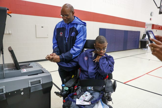 """Tony Taylor helps his son, Jeremiah, 18, cast his first election ballot inside the Wendell Phillips School 63 polling location on Tuesday, Nov. 6, 2018. """"It's his first time voting and it's an honor to help,"""" Taylor said, of his son who is special needs. """"We used a communication device to let him choose who he wanted to vote for,"""" said Jeremiah's mother, Tawonia (not pictured). """"I closed my eyes and told him to choose."""""""