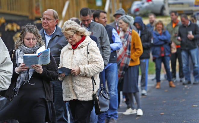 Lisa Busse, from left, Dan Westlund, Jessie Westlund and others bide their time while waiting in line to vote, outside the Chinese Community Church polling site in Hamilton County, for midterm the election, Tuesday, Nov. 6, 2018.