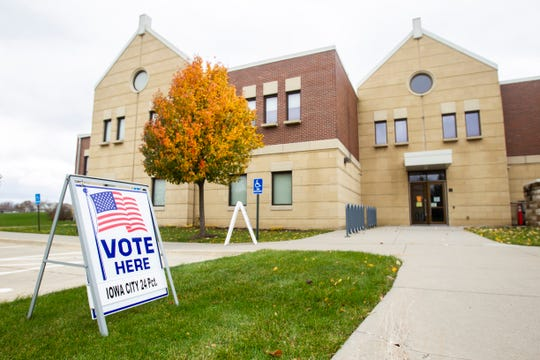 A voting sign directs people towards Iowa City precinct 24 on Tuesday, Nov. 6, 2018, at St. Patrick's Church in Iowa City.