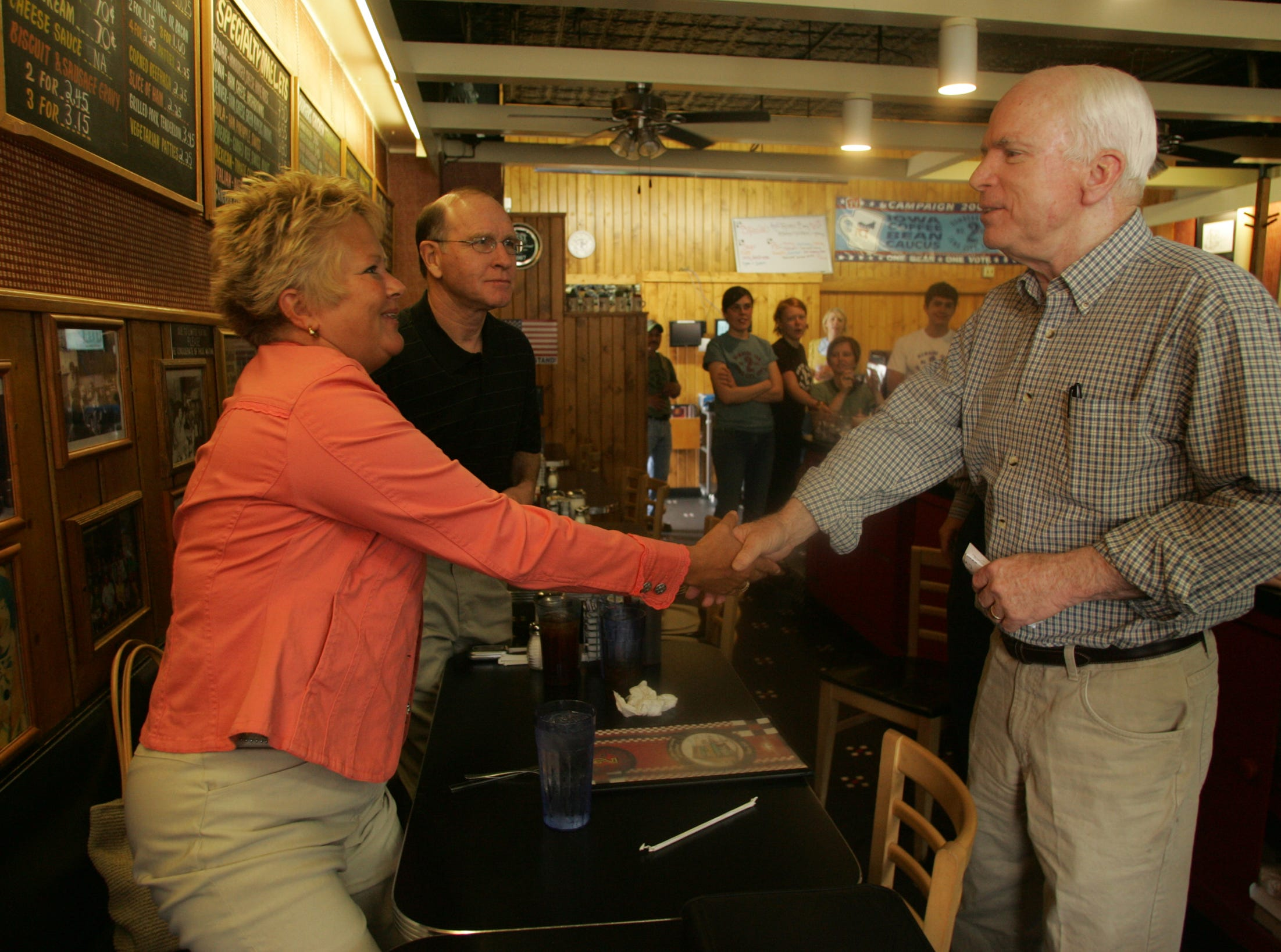 Republican presidential hopeful Sen. John McCain, R-Ariz., right, greets Kathy Gable as her husband, former University of Iowa wrestling coach Dan Gable, looks on at the Hamburg Inn No. 2 in Iowa City on May 7, 2007.