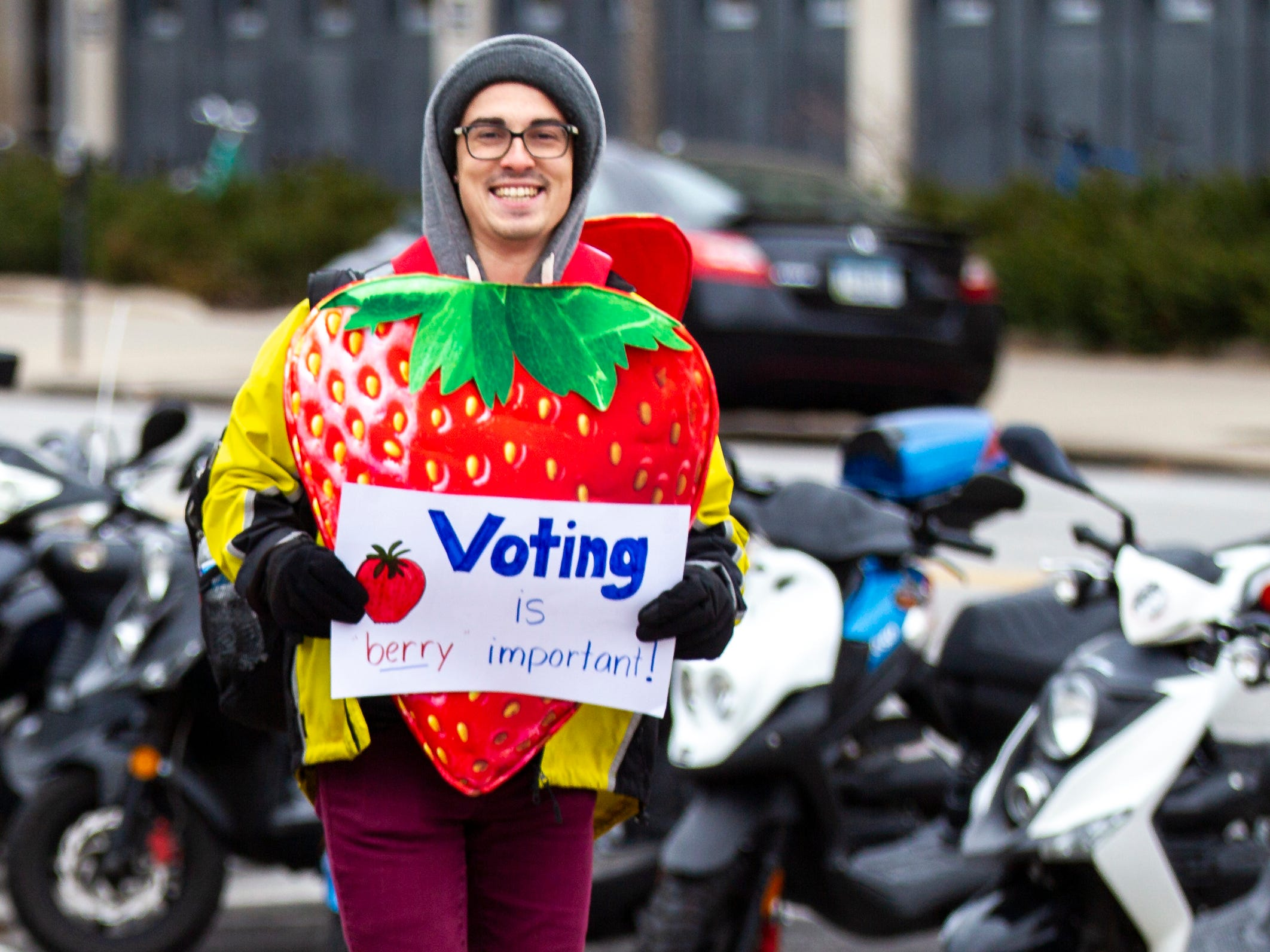 """University of Iowa student Ryan Hall carries a sign reading """"Voting is berry important!"""" while wearing a strawberry costume on Tuesday, Nov. 6, 2018, along Clinton Street Iowa City."""