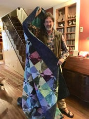 Jonathan Comstock with the quilt he won at the Brooktondale Apple Festival.