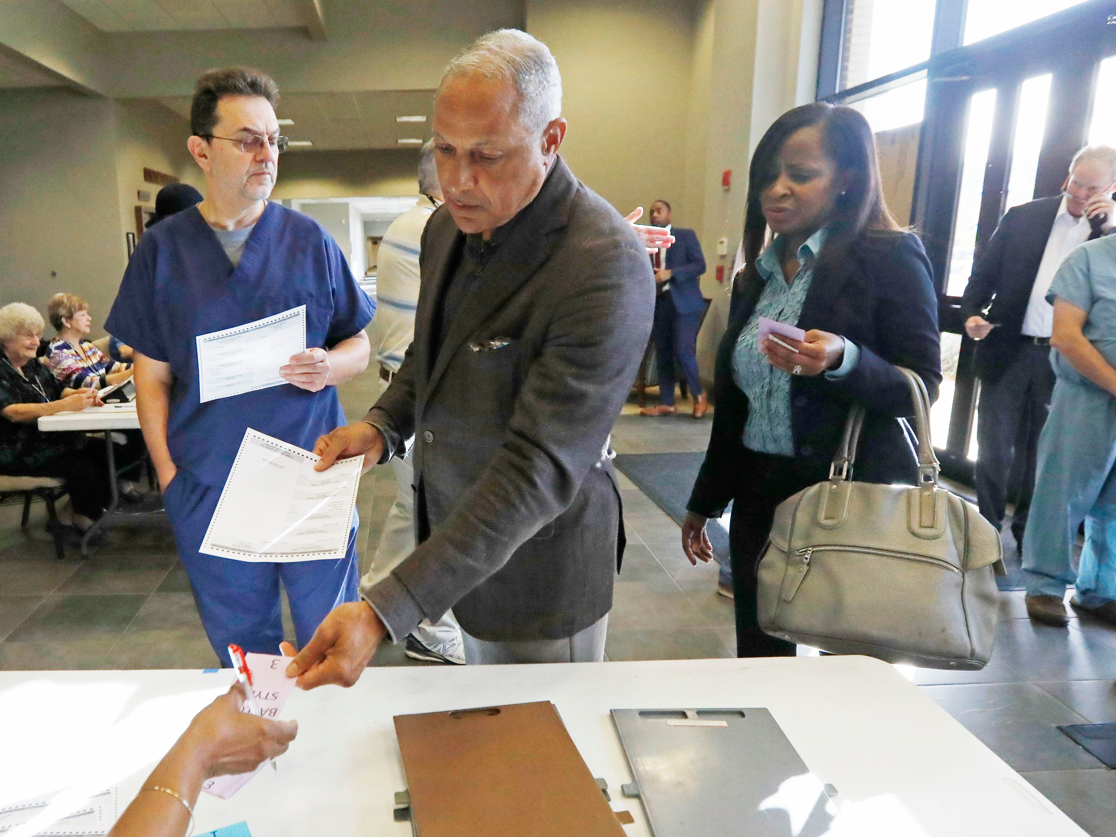 Mississippi Democratic Senatorial candidate Mike Espy, who is seeking to unseat appointed Sen. Cindy Hyde-Smith, R-Miss., hands a poll worker his voting voucher in order to receive a paper ballot, Tuesday, Nov. 6, 2018 in Ridgeland, Miss., as his wife Portia Ballard Espy, right, looks on.
