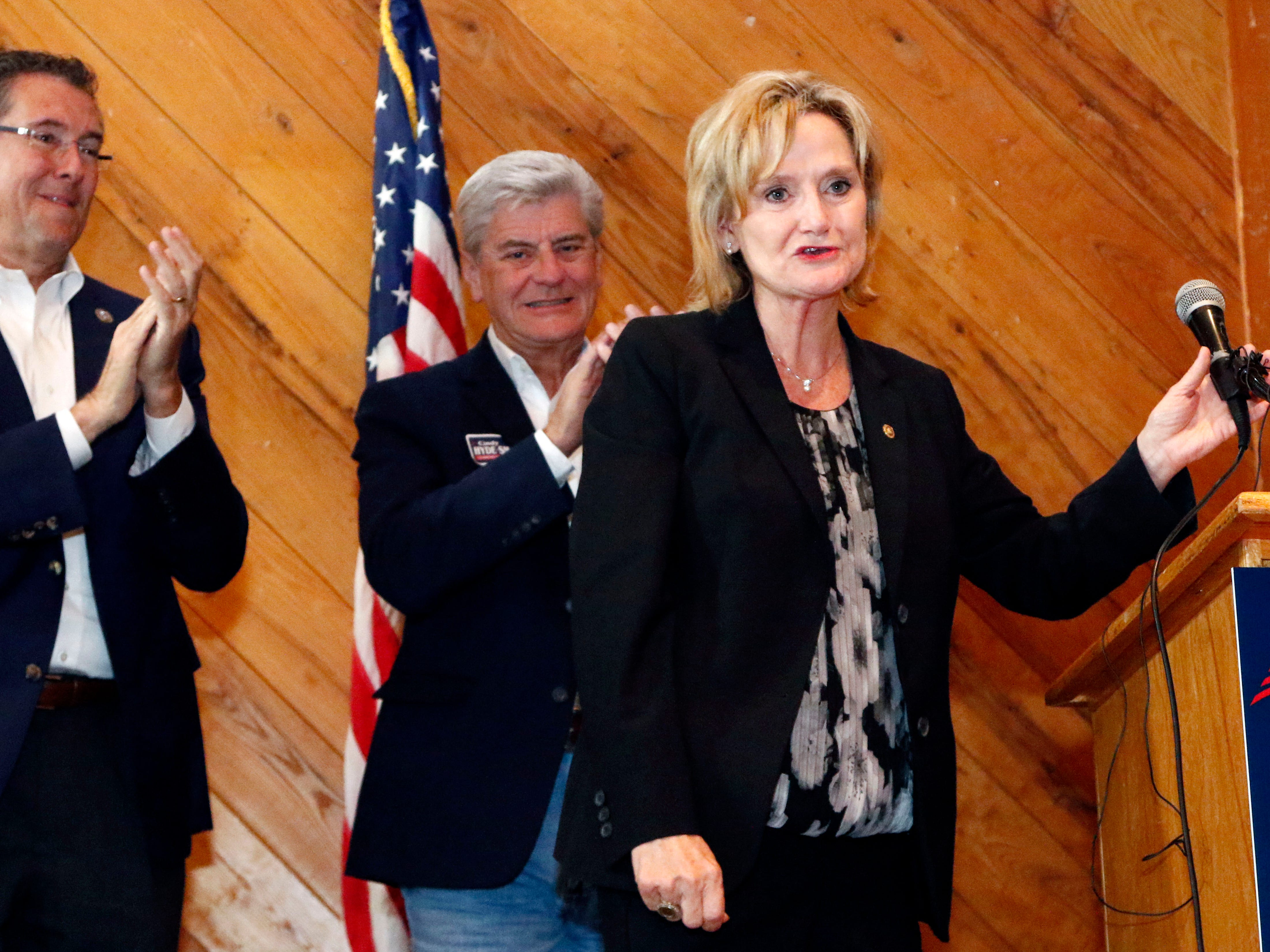 U.S. Rep. Gregg Harper, R-Miss., left, and Gov. Phil Bryant, applaud U.S. Sen. Cindy Hyde-Smith, R-Miss., right, after she spoke to a gathering of supporters in Jackson, Miss., Monday, Nov. 5, 2018.
