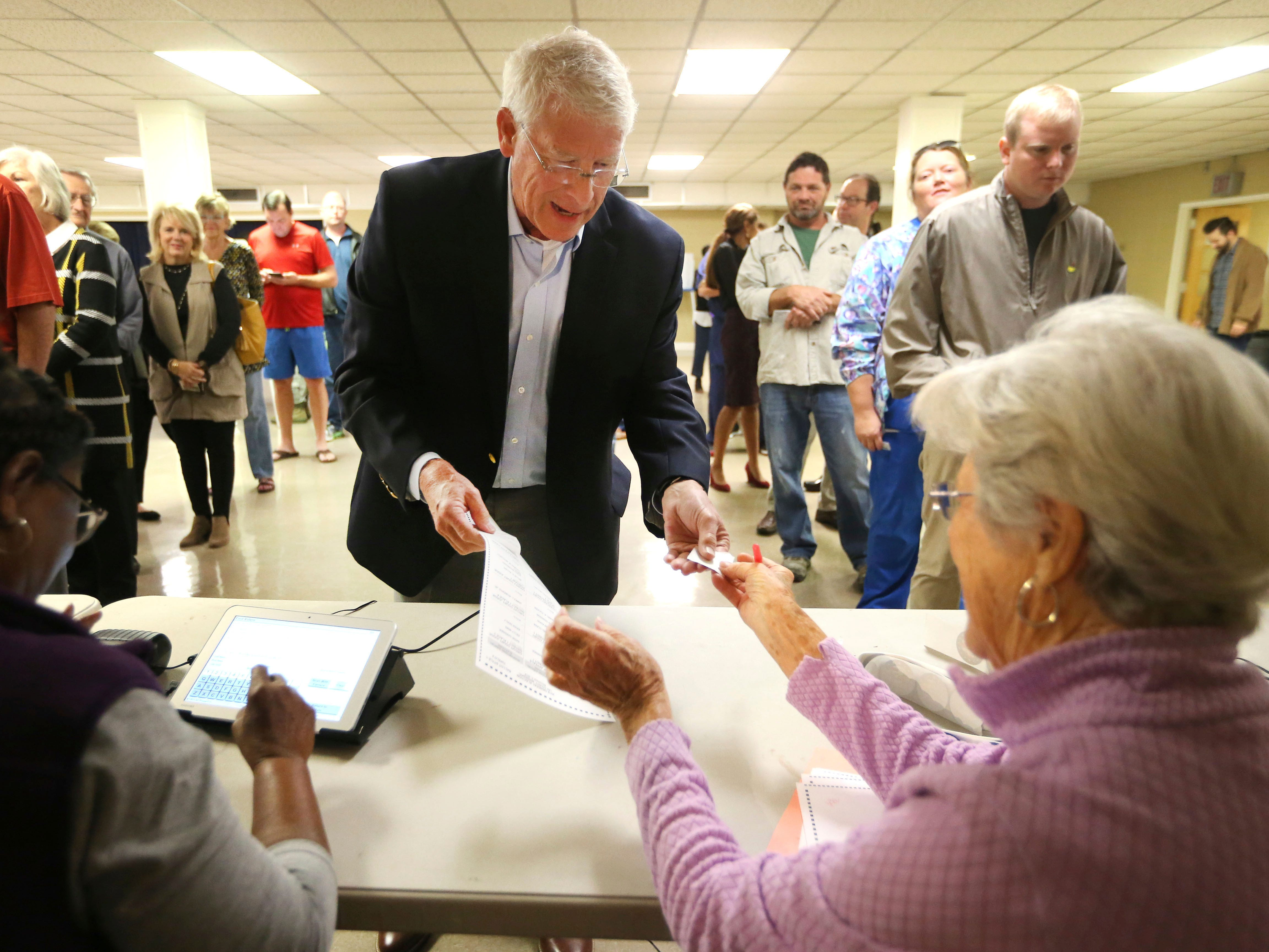 United States Sen. Roger Wicker, R-Miss., center, receives his ballot after showing his voter I.D. and signing in to vote in the midterm elections Tuesday, Nov. 6, 2018, in Tupelo, Miss. Wicker, who seeks reelection, faces several opponents, including State Rep. David Baria, D-Bay St. Louis.
