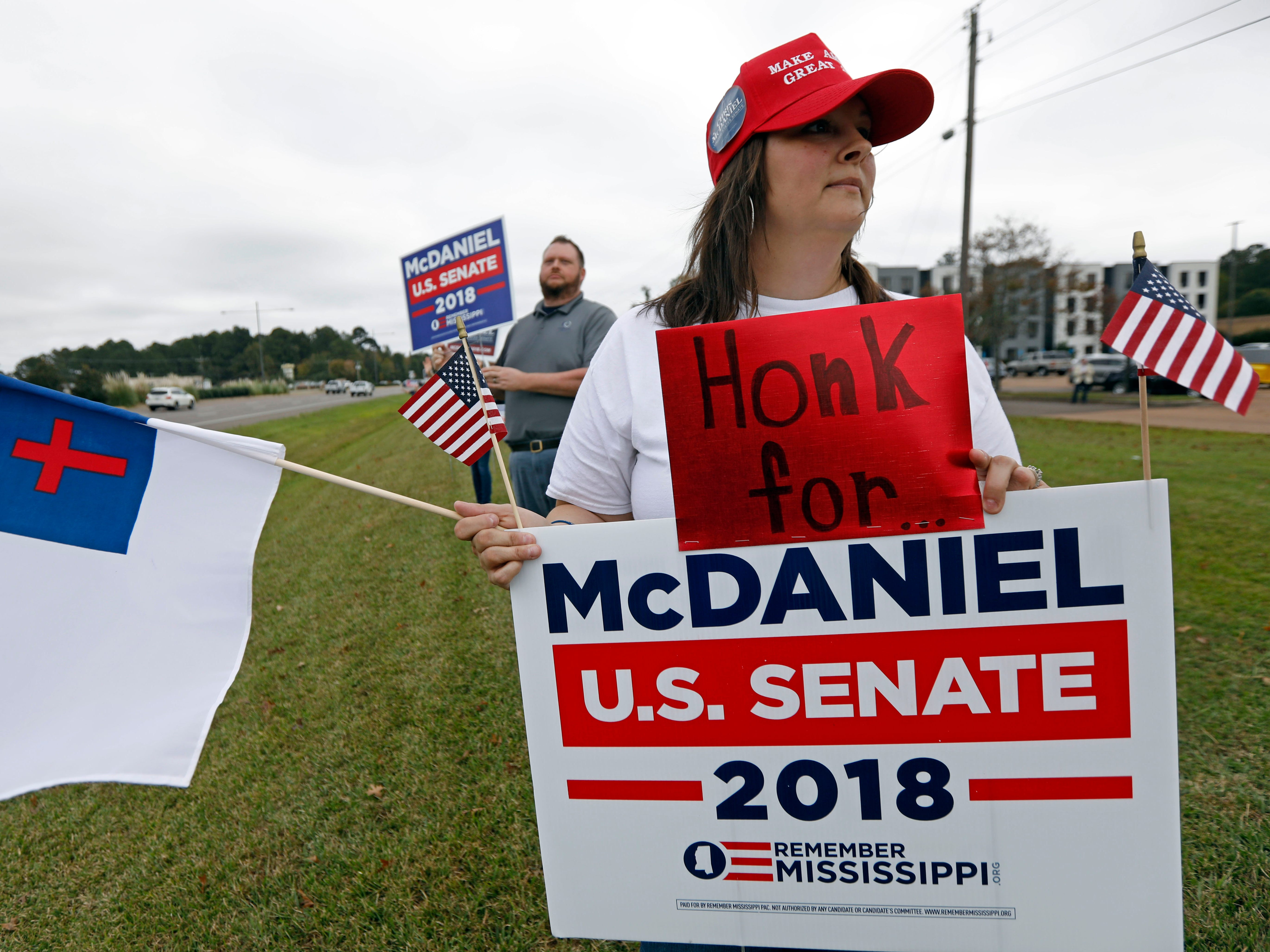 Jennifer Ables of Rankin County, Miss., joins other supporters of State Sen. Chris McDaniel, R-Ellisville, in waving signs and calling out for support along a main thoroughfare in Flowood, Miss., Monday, Nov. 5, 2018.