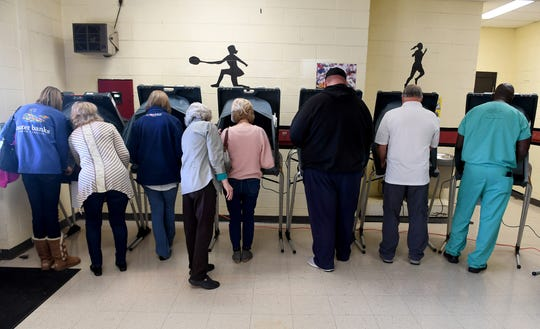 Madison County Election volunteers show some voters how to use the machines before stepping away for voters to cast their ballots in the 2018 midterm elections, Tuesday, November 6.