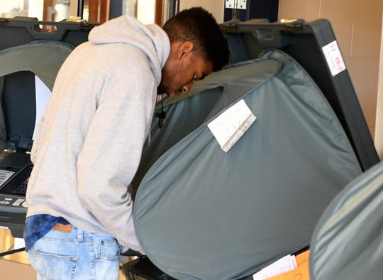 18-year-old Jamir Kyle stands at a voting booth to cast his ballot for the first time at North Side High School during the midterm election, Tuesday, November 6.