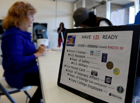 A sign reminding voters to have their photo identification is placed on the table as voters enter to cast their ballots in the 2018 midterm elections, Tuesday, November 6.
