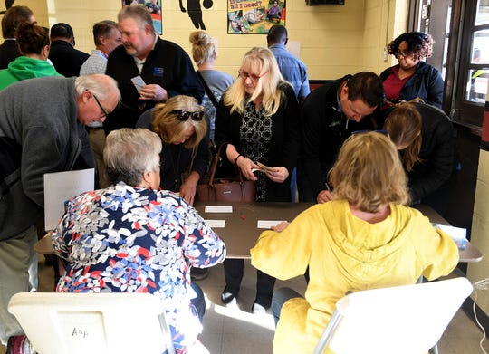 Voter at Pope Elementary make their first top at the sign-in table before going to cast their ballots in the 2018 midterm elections, Tuesday, November 6.