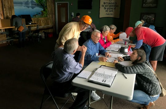 Election officials help voters via lanterns and window light on Tuesday at 65-E at Shoreline Church.