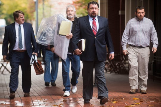Attorney Keith Stewart walks toward the court house on Tuesday in Knoxville, before the closing arguments in a lawsuit filed by the sickened Kingston coal ash workers in the courtyard of the U.S. District Court.