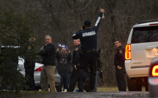 David Henderson, second from left, celebrates with Knox County deputies as Lt. John Hopkins holds up a package removed from the vehicle of a suspect who allegedly attempted to run over an officer on March 3, 2015.
