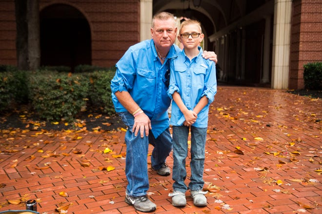 Kingston coal ash spill worker Mike McCarthy and his son Jimmy, 8, pose for a photo before closing arguments in a lawsuit by the sickened workers Nov. 6, 2018.