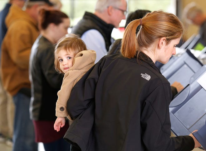 With daughter Hazelle, 1, in her arms, Laura Fearnow casts her ballot Tuesday, November 6, 2018, at Lafayette Fire Department Station 5 at Union Street and Creasy Lane in Lafayette.