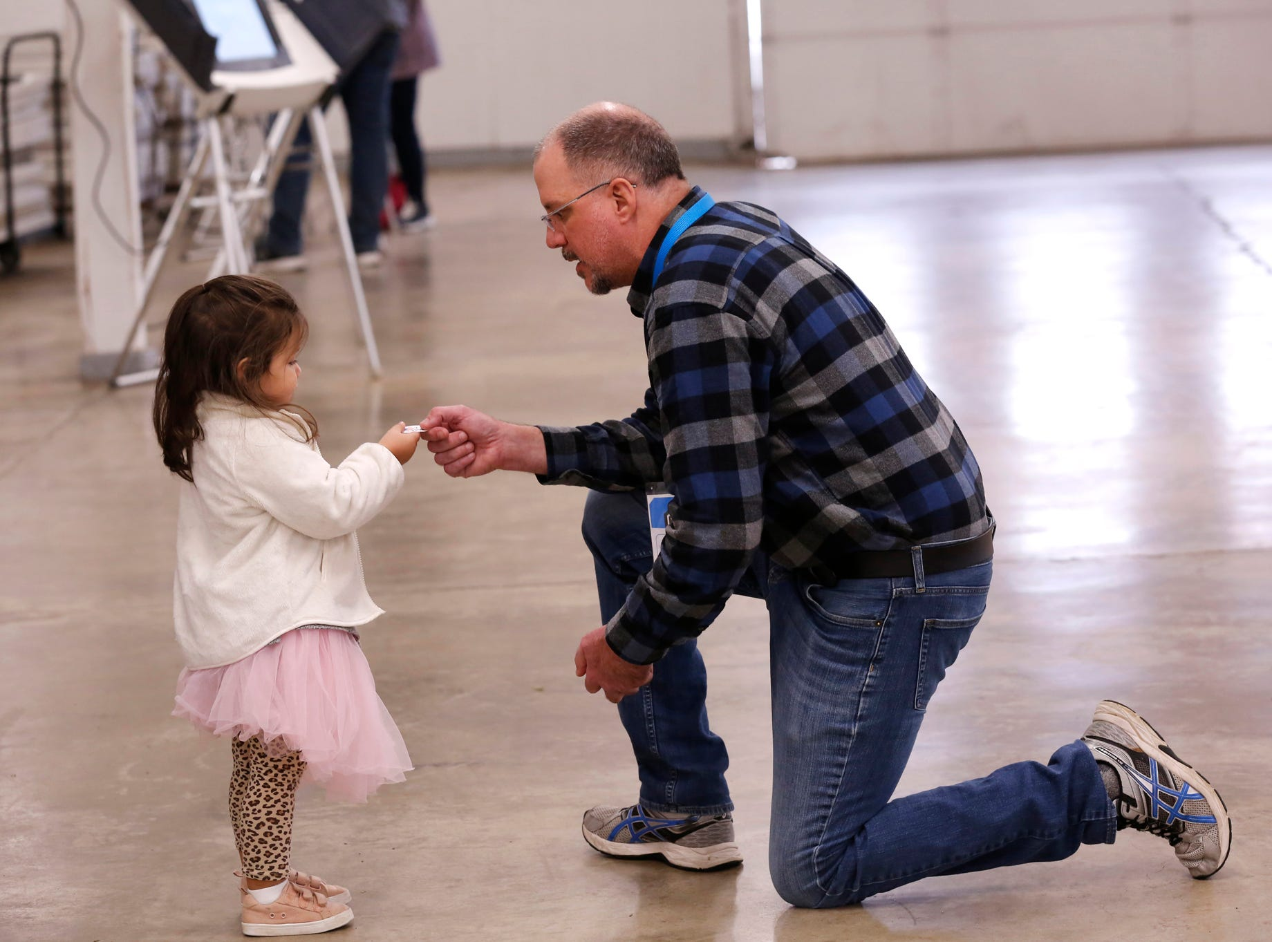 "Lyle Janney gives an ""I Voted"" sticker to Adelynn Toyra, 2, at the Tippecanoe County Fairgrounds Tuesday, November 6, 2018, in Lafayette. The youngster was with Lillian Nize and Karen Toyra, who were voting."