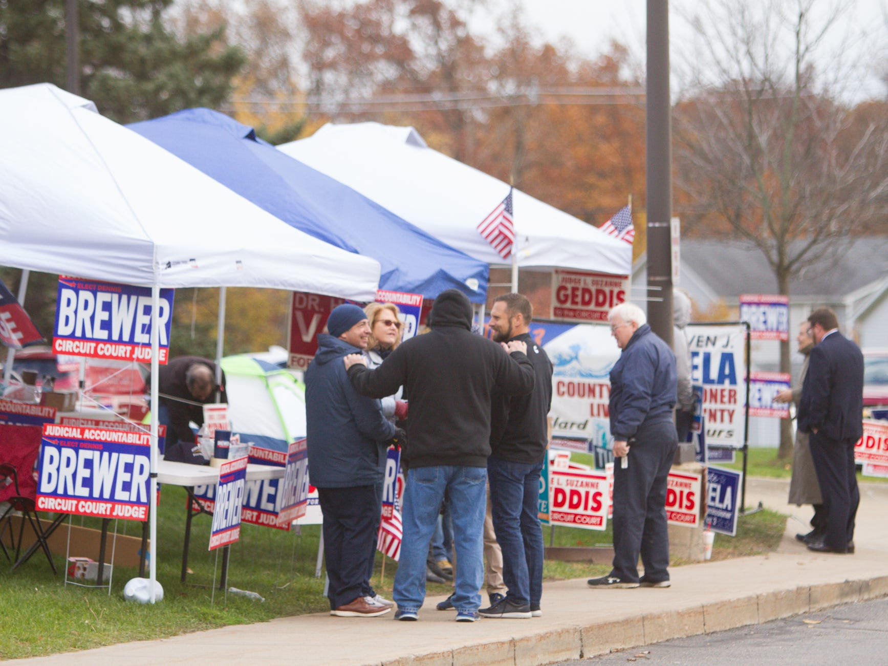 Circuit Court judge candidate Dennis Brewer and 22nd state Senate candidate Lana Theis, left, and others supporting candidates for various races line the parking lot at the Hartland Educational Support Service Center Tuesday, Nov. 6, 2018, a location for five precincts' polls.