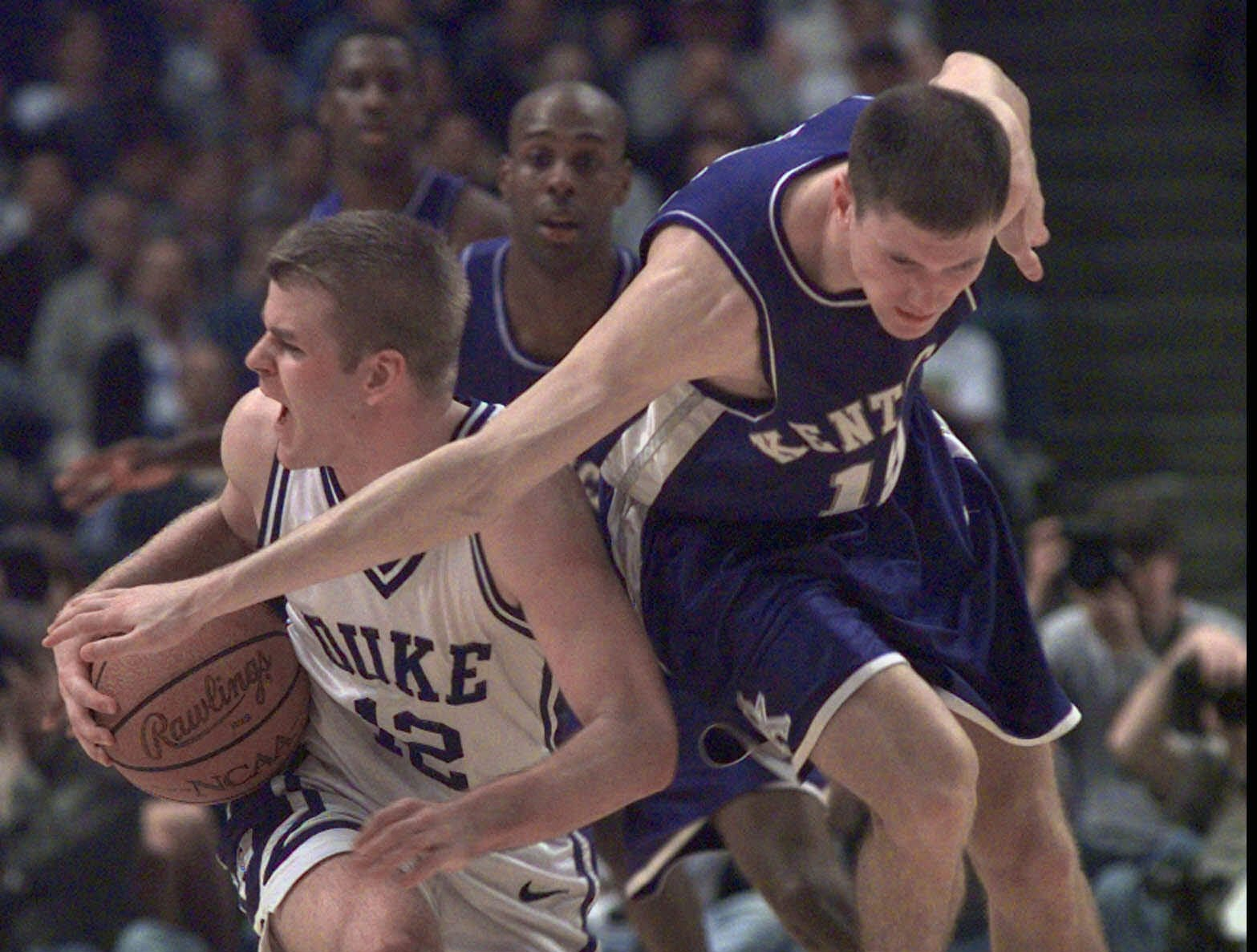 Duke's Steve Wojciechowski (12) tries to hang onto the ball as Kentucky's Jeff Sheppard tries to get possession during action in the NCAA South Regional Final in St. Petersburg, Fla. Sunday, March 22, 1998. Kentucky came on strong in the last minutes of the game and defeated Duke 86-84.