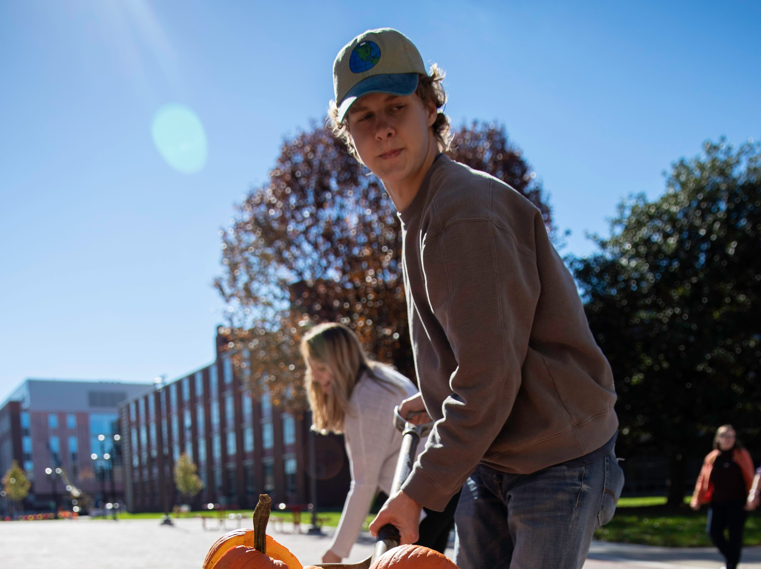 Josh Cagle, sophomore sustainability major, cleans up smashed pumpkins after the annual Pumpkin Smash event, Tuesday, Nov. 6, 2018 in Louisville Ky. The annual Pumpkin Smash in collaboration with the Office of Health Promotion, benefits UofL's Community Composting Project with all smashed pumpkins going into the compost to feed various community gardens, on and off UofL's campus.